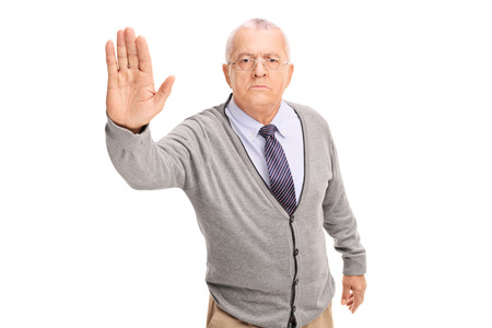 Studio shot of a senior gentleman making a stop gesture with his hand and looking at the camera isolated on white background Banco de Imagens