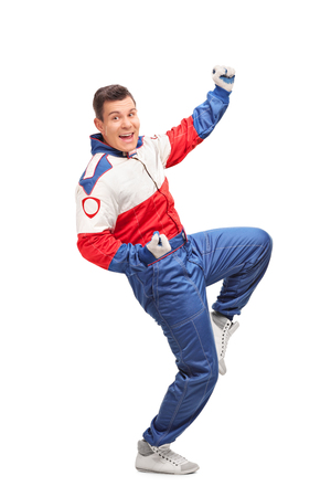 profil: Full length profile shot of an excited car racer throwing his hand in the air and celebrating isolated on white background