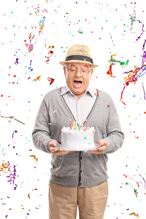 one senior: Vertical shot of an overjoyed senior holding a birthday cake with confetti streamers flying around him isolated on white background