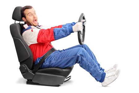 Studio shot van een jonge auto racer doen alsof ze heel snel gezeten op een auto zitten op een witte achtergrond te rijden