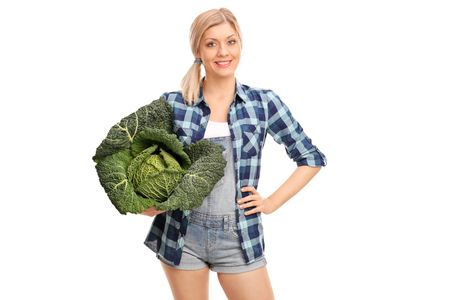 confident woman: Young woman holding a Savoy cabbage in her hand and looking at the camera isolated on white background