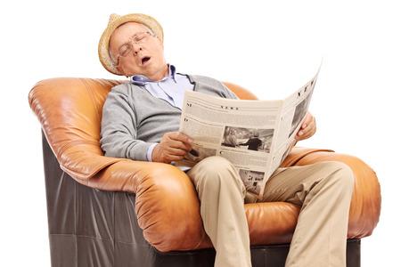 Studioaufnahme der ein Senior Mann schläft auf einem Sessel und hält eine Zeitung in der Hand isoliert auf weißem Hintergrund
