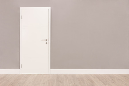 Shot of a closed white door on a gray wall in an empty room Archivio Fotografico