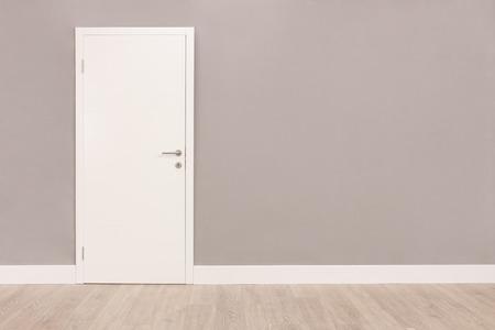 Shot von einem geschlossenen weißen Tür auf einer grauen Wand in einem leeren Raum Standard-Bild - 50301395