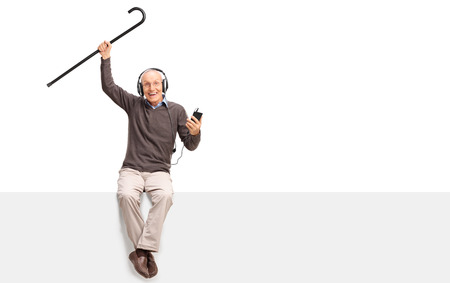 Senior man listening to music on headphones and lifting his cane in the air seated on a blank panel isolated on white background Stock Photo