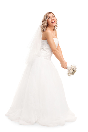 tossing: Full length portrait of a young blond bride tossing her wedding bouquet isolated on white background Stock Photo