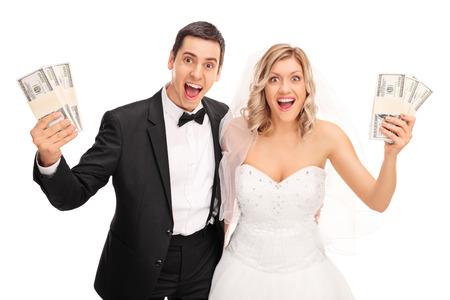 Happy newlywed para trzymając się za kilka stosów pieniędzy i patrząc na kamery na białym tle