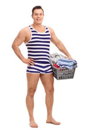 ropa interior: Retrato de cuerpo entero de un joven en una ropa interior de rayas sosteniendo un cesto de la ropa llena de ropa aislado en el fondo blanco