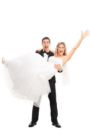 Full length Portret van een jonge bruidegom tillen zijn bruid in zijn handen op een witte achtergrond