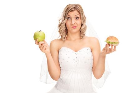 Jonge bruid met een appel in de ene hand en een hamburger in de andere op een witte achtergrond Stockfoto
