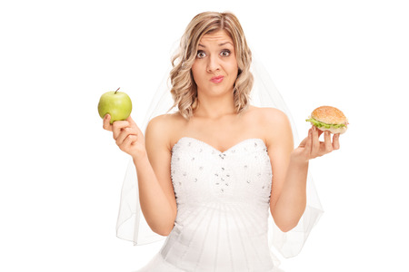 1: Young bride holding an apple in one hand and a hamburger in the other isolated on white background