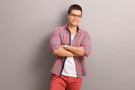 uomo rosso: Casual giovane uomo in una camicia rossa a scacchi in posa e appoggiato a un muro grigio