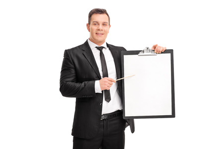 suit: Young businessman holding a clipboard with a blank paper on it and pointing towards it with a stick isolated on white background