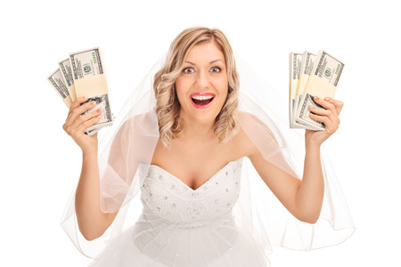 few: Young bride in a white wedding dress holding few stacks of money isolated on white background Stock Photo