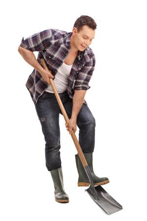 Portret pełnej długości młodych rolnik z butów gumowych kopanie z łopatą samodzielnie na białym tle