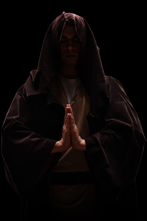 priest's ritual robes: Vertical shot of a monk with a hood on his head praying on black background Stock Photo