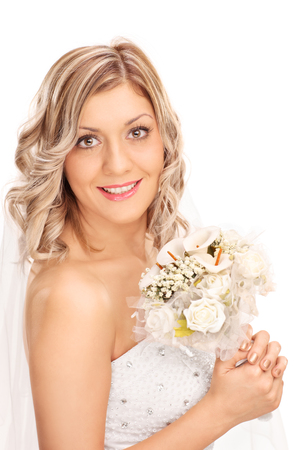 bride dress: Vertical shot of a young blond bride holding a wedding flower and posing in a white wedding dress isolated on white background Stock Photo