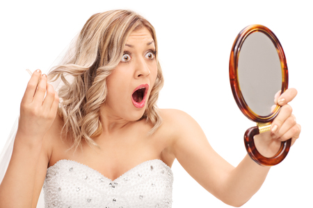 Jeune mariée furieux regardant sa coiffure dans un miroir isolé sur fond blanc
