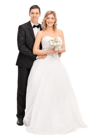 Volledige lengte portret van een jonge bruid en bruidegom poseren samen op een witte achtergrond