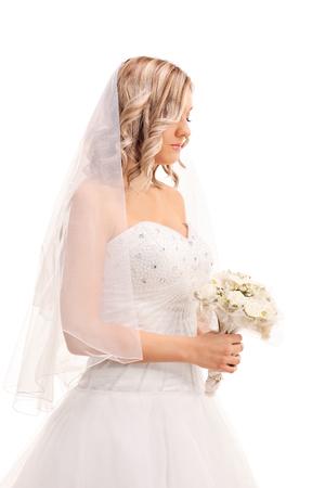 mujer sola: Tiro vertical de una joven novia preocupado caminando con una flor de la boda y mirando hacia abajo aislado en el fondo blanco Foto de archivo