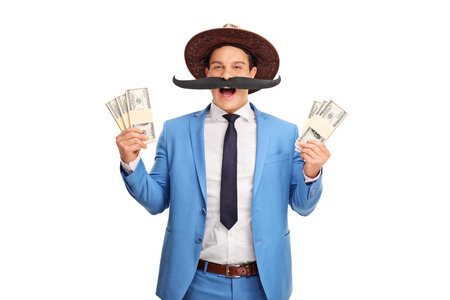 fake money: Young man with a fake moustache and a cowboy hat holding few stacks of money isolated on white background