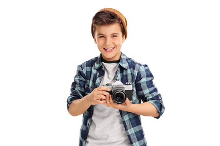 Cool little boy with a brown hat and checkered shirt holding a camera and smiling isolated on white background