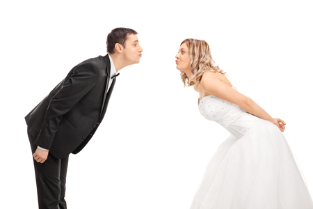 passionate kissing: Young bride and groom standing opposite of each other and going in for a kiss isolated on white background