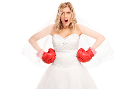 tough girl: Angry bride in a white wedding dress and red boxing gloves looking at the camera isolated on white background