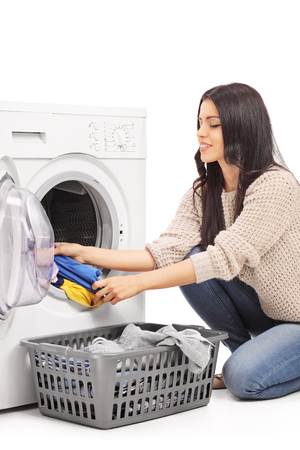 emptying: Vertical shot of a young woman emptying a washing machine isolated on white background