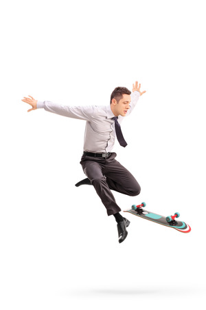 midair: Full length portrait of a young businessman performing tricks with a skateboard shot in mid-air isolated on white background