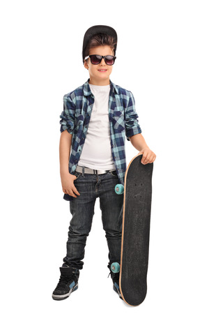sunglasses isolated: Full length portrait of a cool little skater boy with a cap and black sunglasses isolated on white background