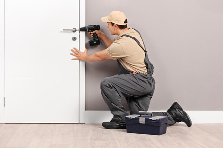 Young male locksmith installing a lock on a new white door with a hand drill