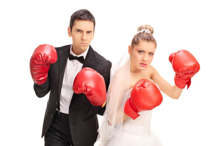 boxing glove: Studio shot of an angry newlywed couple posing with red boxing gloves isolated on white background