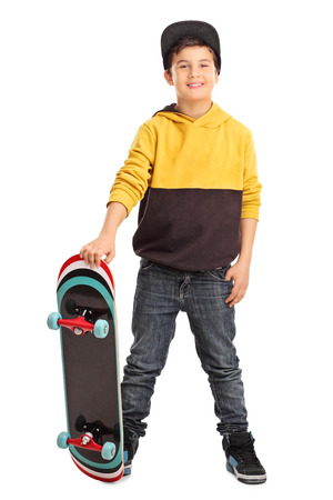 boy skater: Full length portrait of a cute little skater boy holding a skateboard and looking at the camera isolated on white background Stock Photo