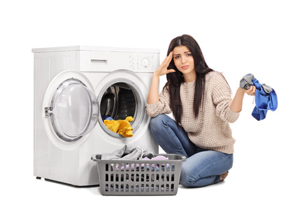 Studio shot of a sad woman emptying a washing machine and looking at the camera isolated on white background