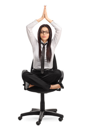 meditation isolated white: Vertical shot of a young businesswoman practicing yoga seated on an office chair isolated on white background