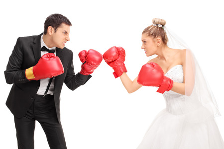 girl fighting: Young groom and a bride fighting each other with boxing gloves isolated on white background