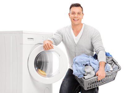 man laundry: Content young man holding a laundry basket and standing next to a washing machine isolated on white background