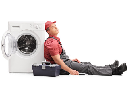 powerless: Exhausted young plumber sitting by a washing machine and looking up isolated on white background