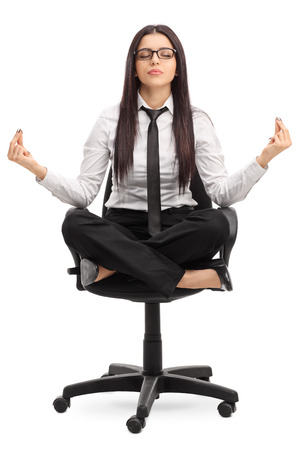 mojo: Vertical shot of a young beautiful businesswoman meditating seated on an office chair isolated on white background Stock Photo