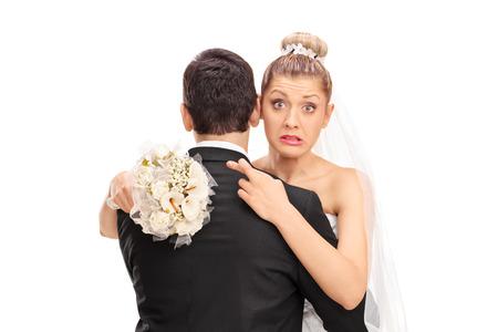 Jonge blonde bruid knuffelen haar man met haar vingers gekruist op een witte achtergrond