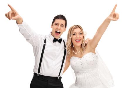 cantando: Novia y novio alegres cantando juntos y apuntando hacia arriba con las manos aisladas en fondo blanco Foto de archivo