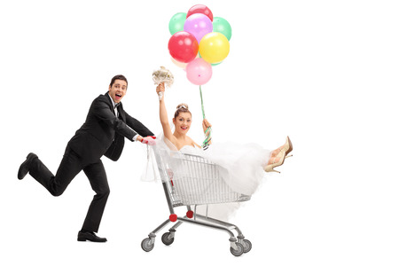 bride and groom background: Full length portrait of a groom pushing the bride in a shopping cart isolated on white background Stock Photo