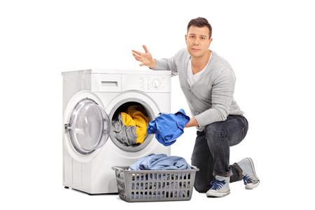 emptying: Sad young guy emptying a washing machine isolated on white background