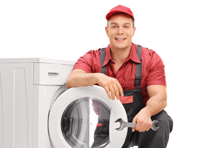 posing: Young cheerful plumber holding a wrench and posing next to a washing machine isolated on white background