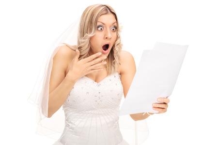 Geschokt blonde bruid op zoek naar een stuk papier in ongeloof op een witte achtergrond