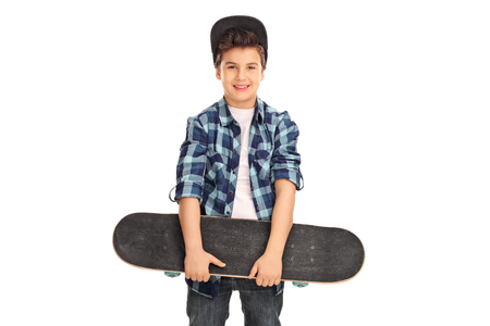 Little kid with a blue cap and checkered shirt holding a skateboard isolated on white background Stock Photo
