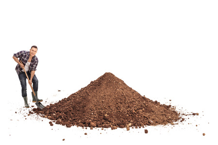 shoveling: Young manual worker shoveling a pile of dirt and looking at the camera isolated on white background Stock Photo
