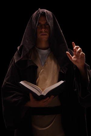 preaching: Vertical shot of a mysterious monk holding a book and preaching on black background Stock Photo