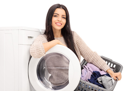 machine: Young cheerful housewife holding a laundry basket and posing next to a washing machine isolated on white background